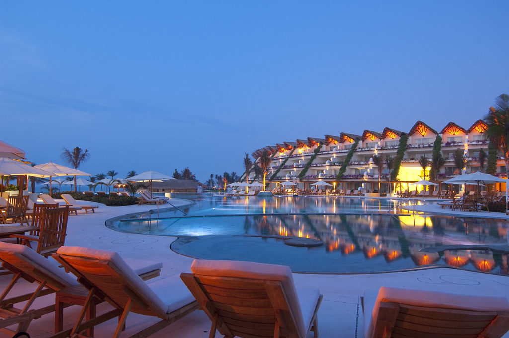 large resort hotel in the distance at dusk with a curved pool & red chaise lounges