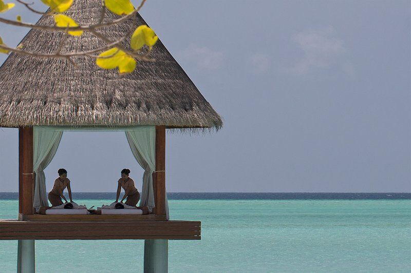 couples massage in an elevated thai hut over the sea