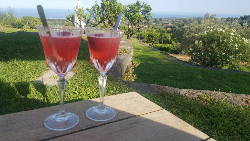 2 prepared cocktails on a ledge with the Sicilian countryside in the background