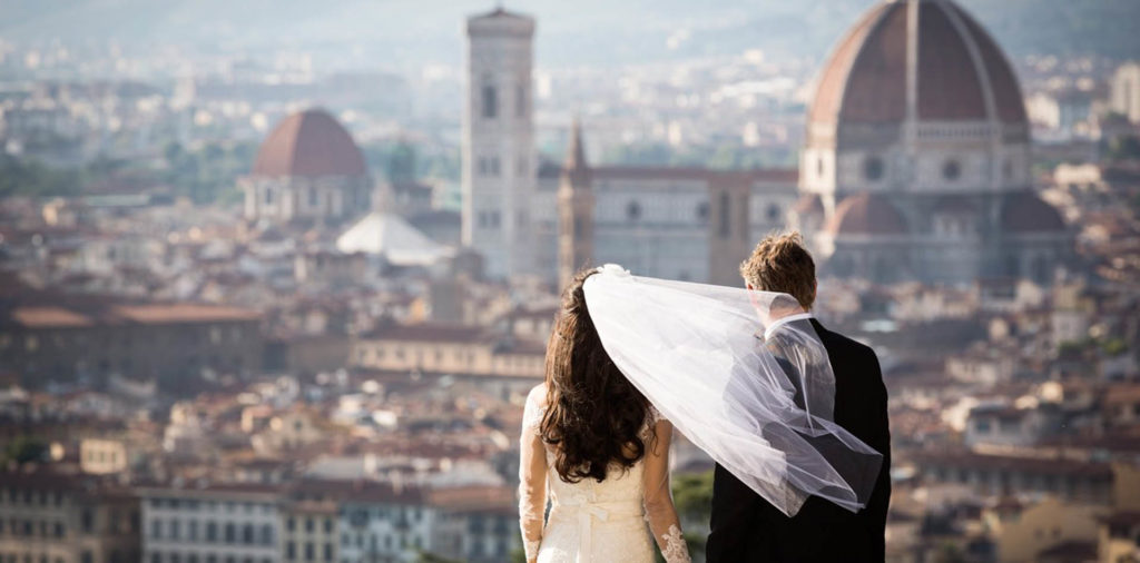 Wedding couple with veil in the wind overlooking Florence Italy
