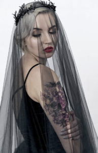 bride wearing black headpiece, black sleeveless dress & balck lace veil with red lipstick