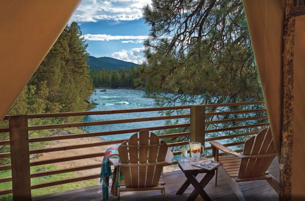2 empty adirondak chairs facing a raging river from a luxury hotel balcony